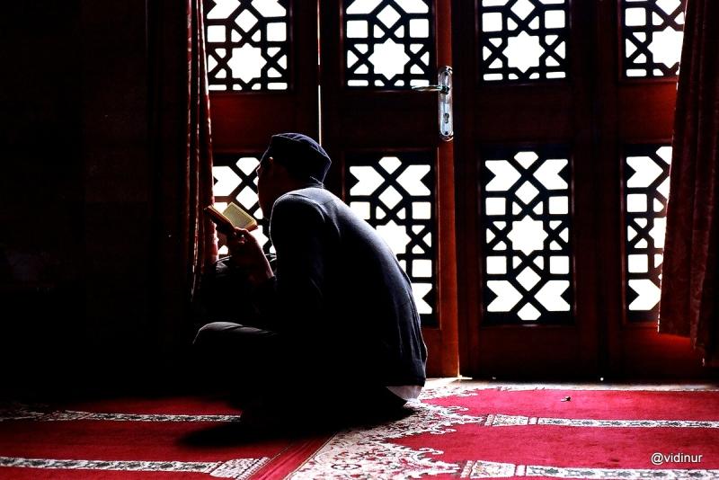 Ketika masuk masjid untuk sholat duhur, saya melihat seseorang sedang membaca alquran di samping pintu yang berornamen...
